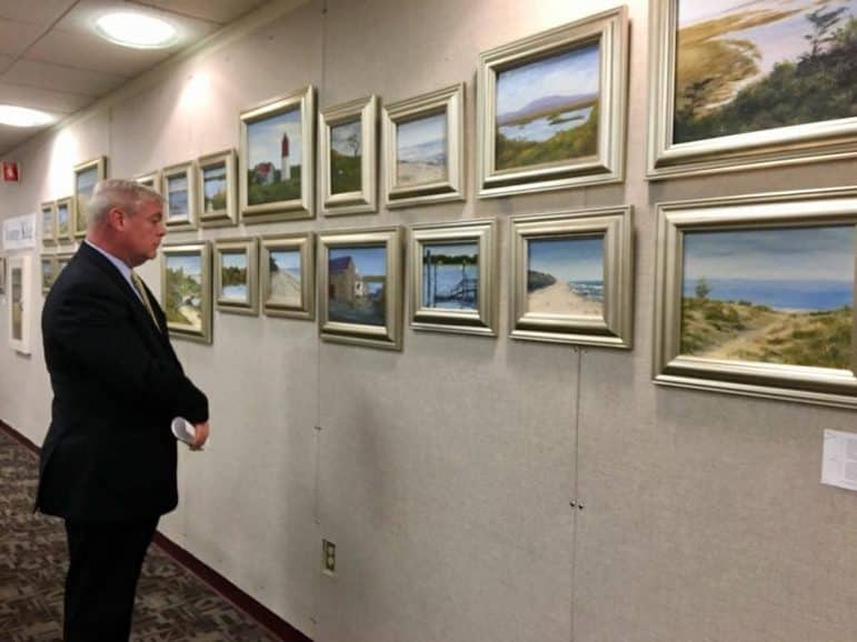 [CREDIT: Mayor Scott Avedisian's office] Mayor Scott Avedisian views paintings by Yvonne King of Galway, Ireland on display at the Warwick Public Central Library.