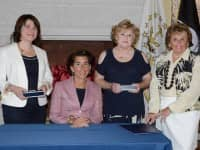 Sen. Gayle L. Goldin (D-Dist 3, Providence) left, and Rep. Eileen S. Naughton (D-Dist. 21, Warwick) third from left, join Gov. Gina Raimondo (seated) at a ceremonial bill signing today for the Caregiver Advise, Record and Enable Act. At right is AARP Rhode Island State Director Kathleen Connell.