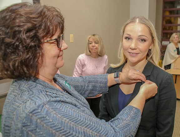 [CREDIT: CCRI] Irina V. Diffley of Warwick recently was inducted into the Gamma Lambda Chapter of Alpha Delta Nu nursing honor society at CCRI. Pictured above, Professor Linda A. Ethier pins Diffley at the ceremony.