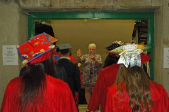 {CREDIT: Rob Borkowski] Toni Anderson, secretary at Toll Gate High, high-fives Class of 2019 graduates as they march into the CCRI field house for graduation.