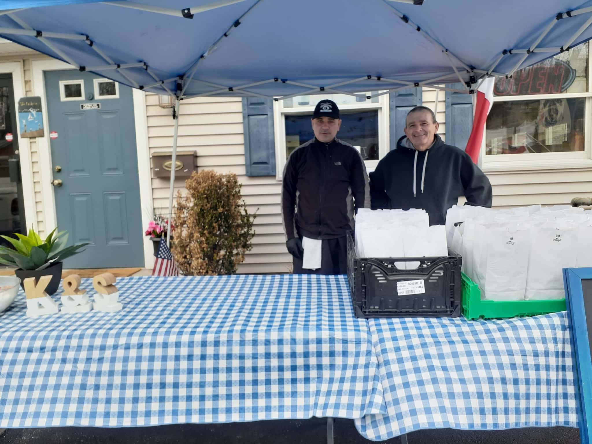 [COURTESY PHOTO] Kim-&-Steve's-Masthead-Grill is giving free take-out lunches to shut-in families during the COVID-19 outbreak. Restaurant employees, from left, Chuckie and Gary, were handing out the lunches Monday.