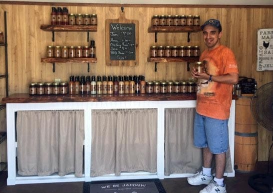 [CREDIT: Debbie Wood] Jason Wood, proprietor of We Be Jamming, at his shed/shop in Warwick on West Shore Road, with a wide selection of jams and spreads for sale.
